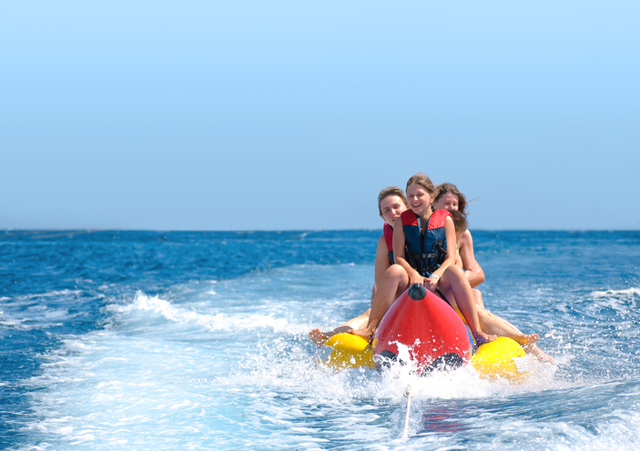 A group of friends ride on a banana boat