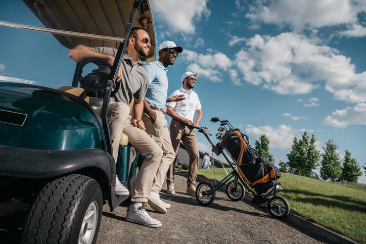 A group of friends watch a fellow golfer swing