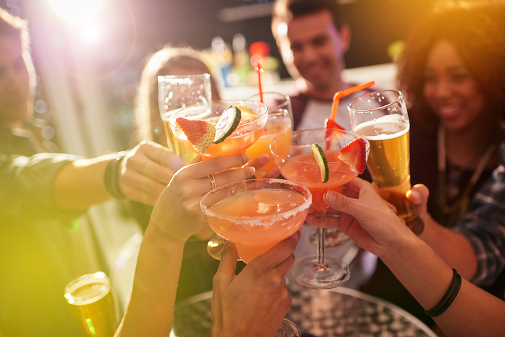 A group of friends cheers a round of drinks